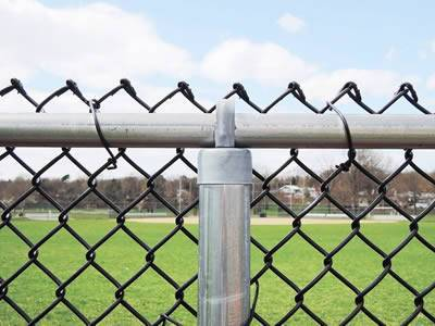 A black chain link fence with a thick horizontal rail and a vertical post.