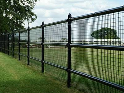 There is a welded cattle fence with several rough posts and horizontal rails on the grassland.